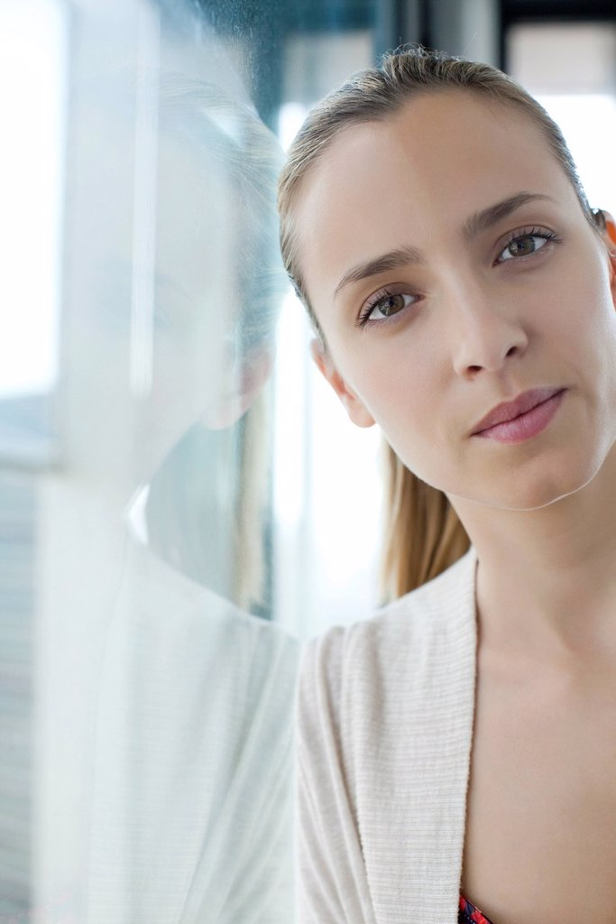 Woman leaning against window : Stock Photo