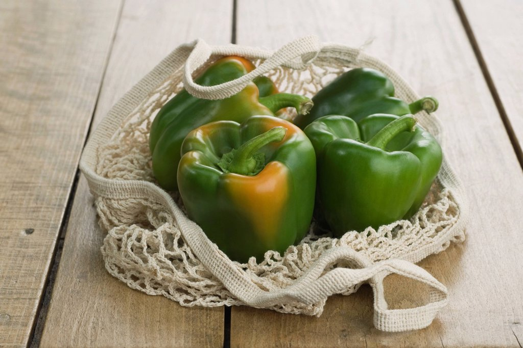 Fresh green bell peppers in mesh shopping bag : Stock Photo
