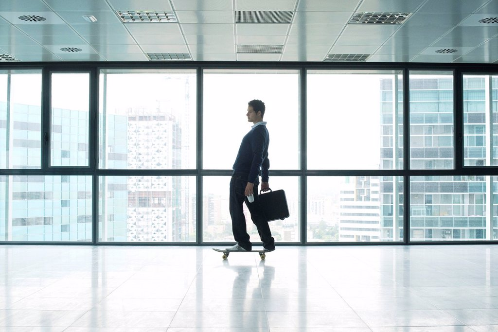 Stock Photo: 1569R-9072614 Businessman standing on skateboard with briefcase