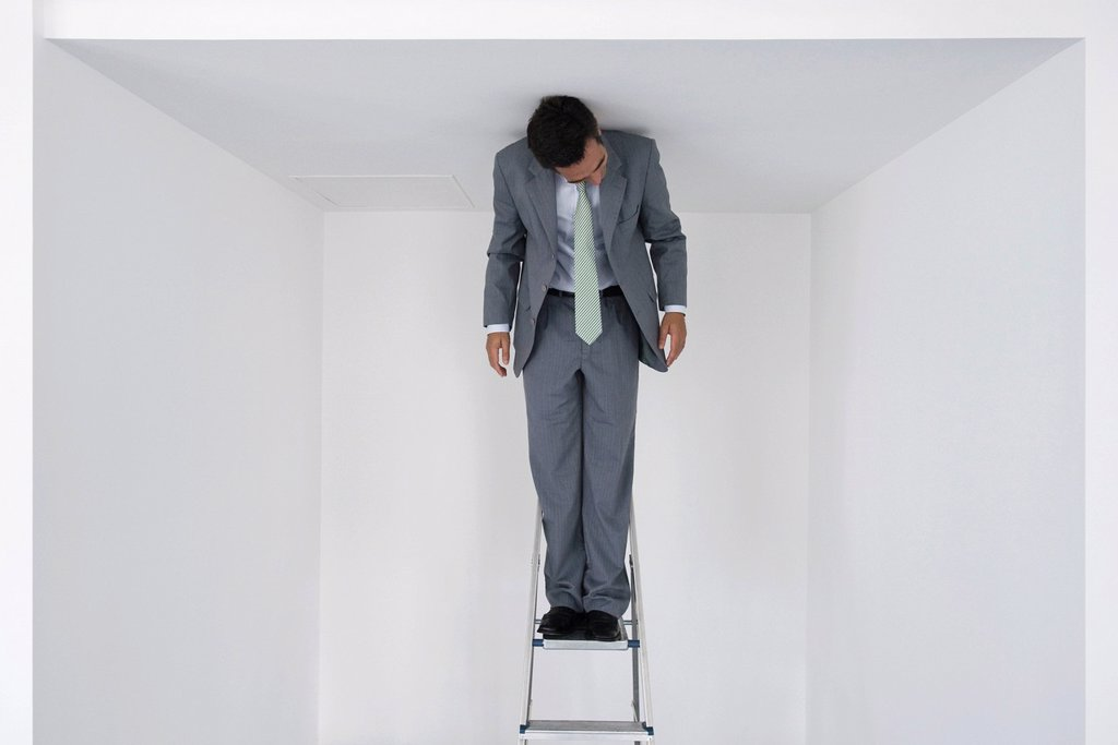 Stock Photo: 1569R-9072660 Executive standing on stepladder