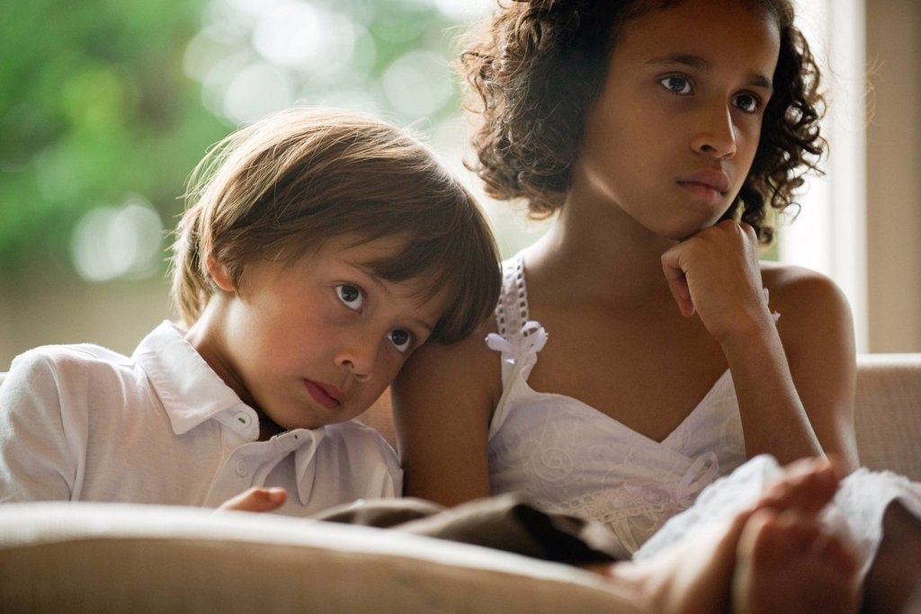Stock Photo: 1569R-9072777 Children watching TV together, boy resting head on sister´s shoulder