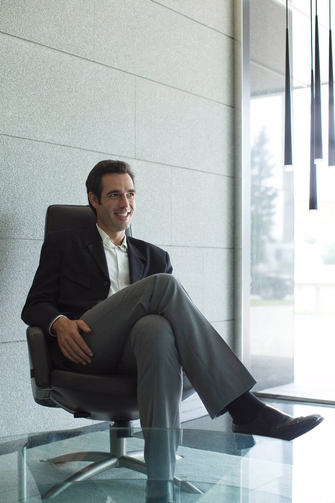 Stock Photo: 1569R-9072802 Executive sitting in lobby, backlit