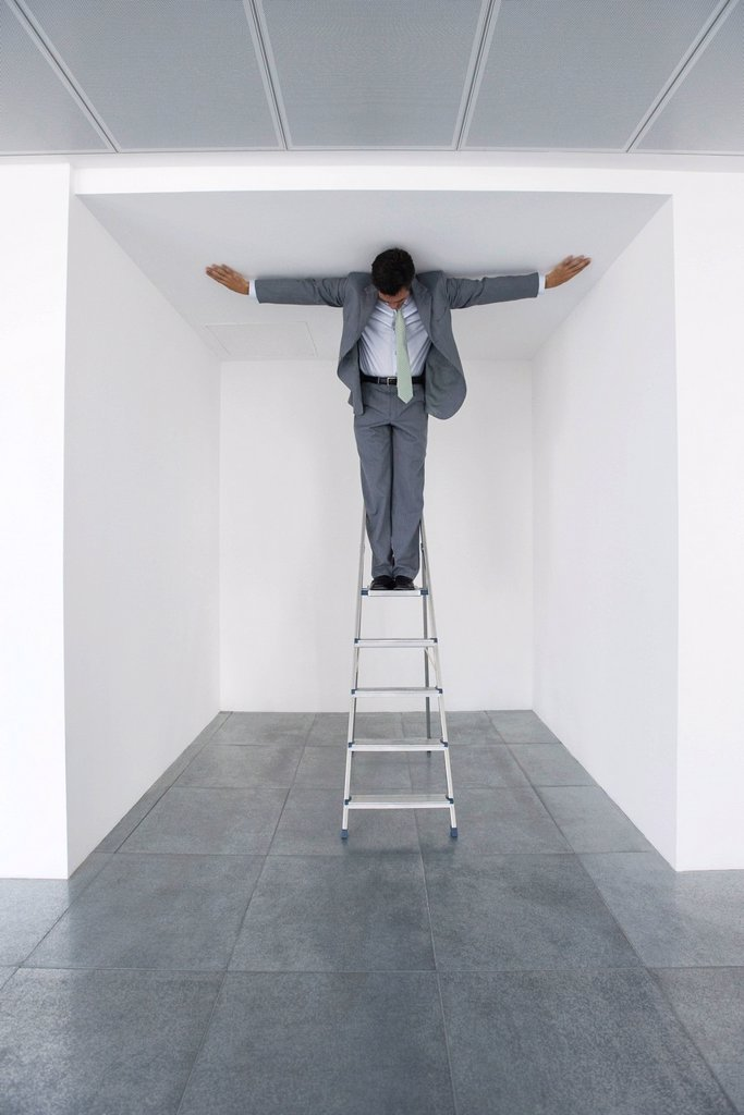 Executive standing on stepladder, arms outstretched on ceiling : Stock Photo