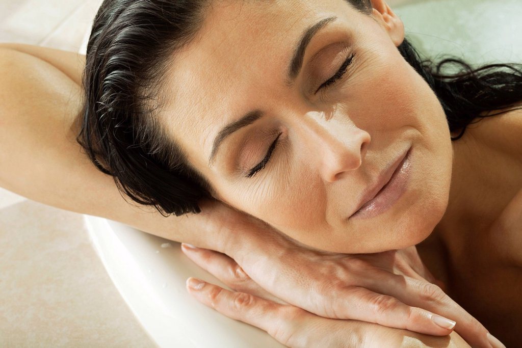 Stock Photo: 1569R-9072872 Woman resting head on arms relaxing in bath