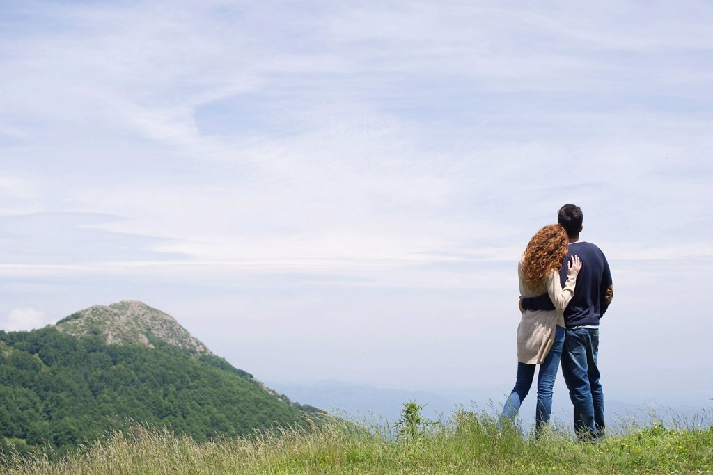 Couple enjoying scenic mountain view, rear view : Stock Photo
