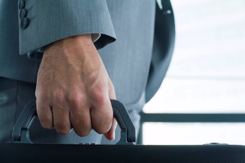 Executive´s hand carrying briefcase, mid section, close_up : Stock Photo
