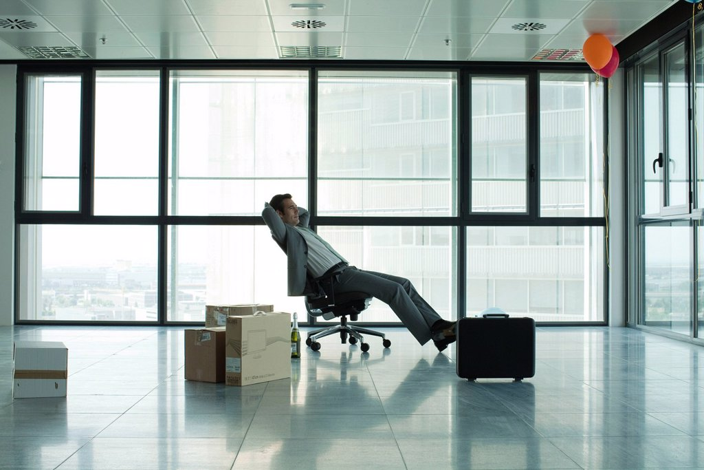Businessman sitting in empty office with boxes on floor : Stock Photo