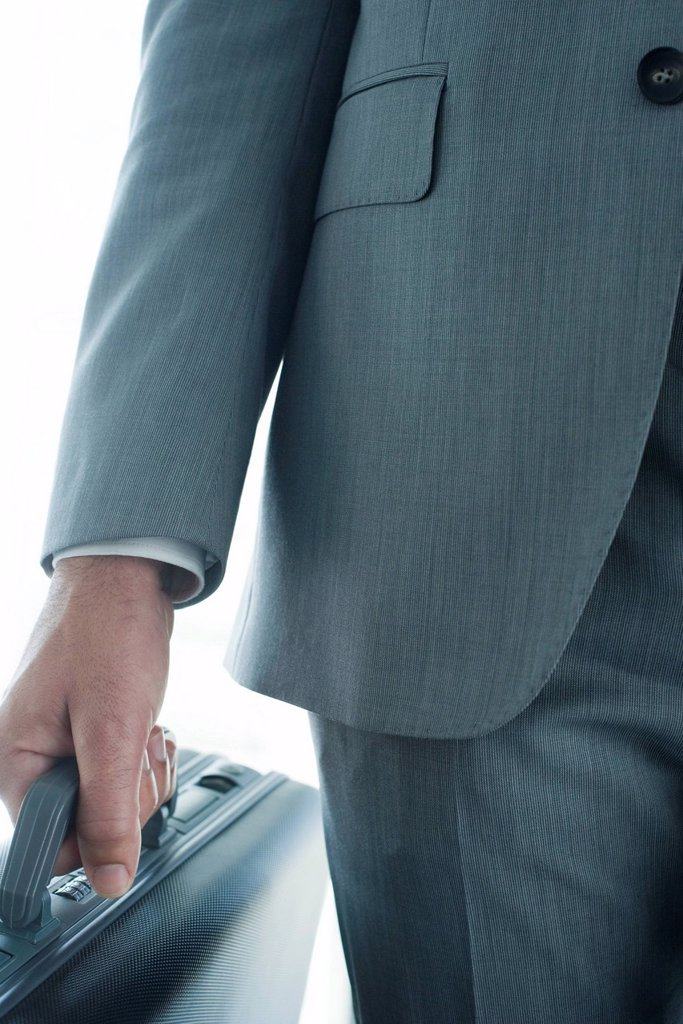 Stock Photo: 1569R-9073010 Executive carrying briefcase, mid section