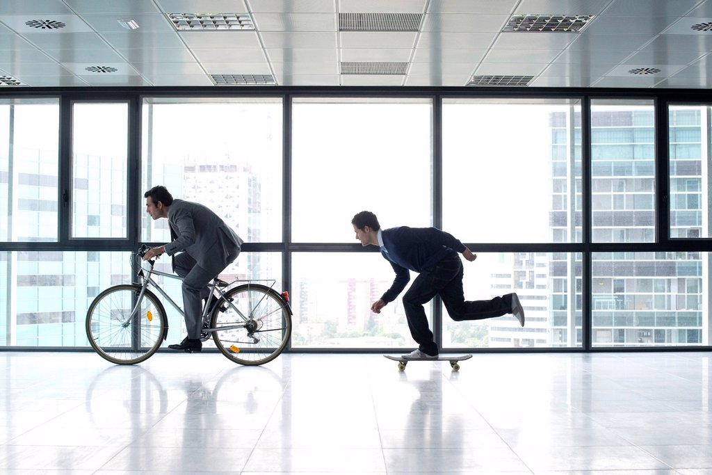 Stock Photo: 1569R-9073163 One businessman riding bicycle, the other skateboarding