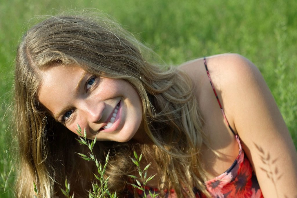 Stock Photo: 1569R-9073175 Young woman relaxing in tall grass, portrait