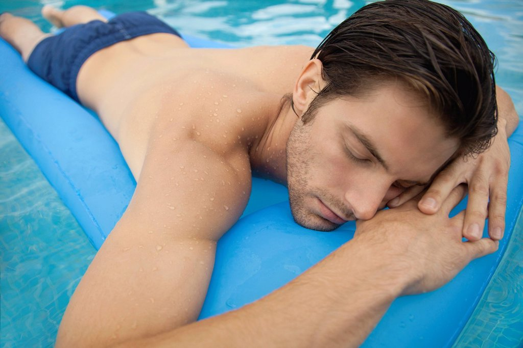 Young man lying on stomach on inflatable float : Stock Photo