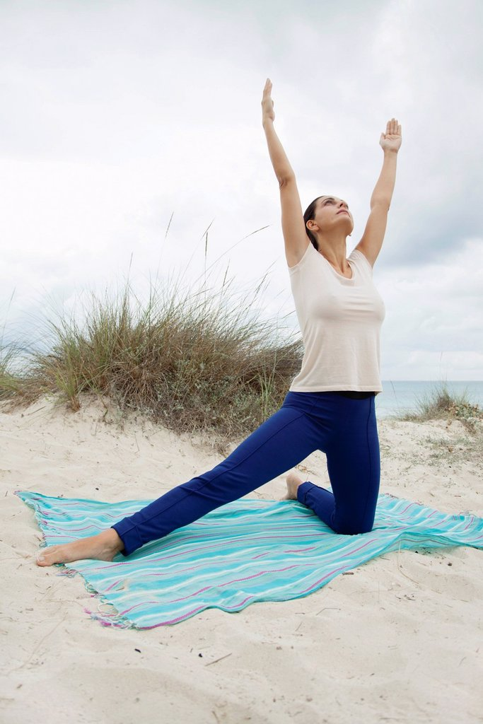 Mature woman practicing yoga on beach : Stock Photo