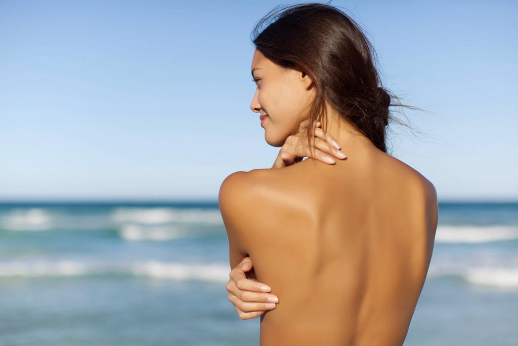 Stock Photo: 1569R-9073469 Naked young woman looking at ocean, rear view