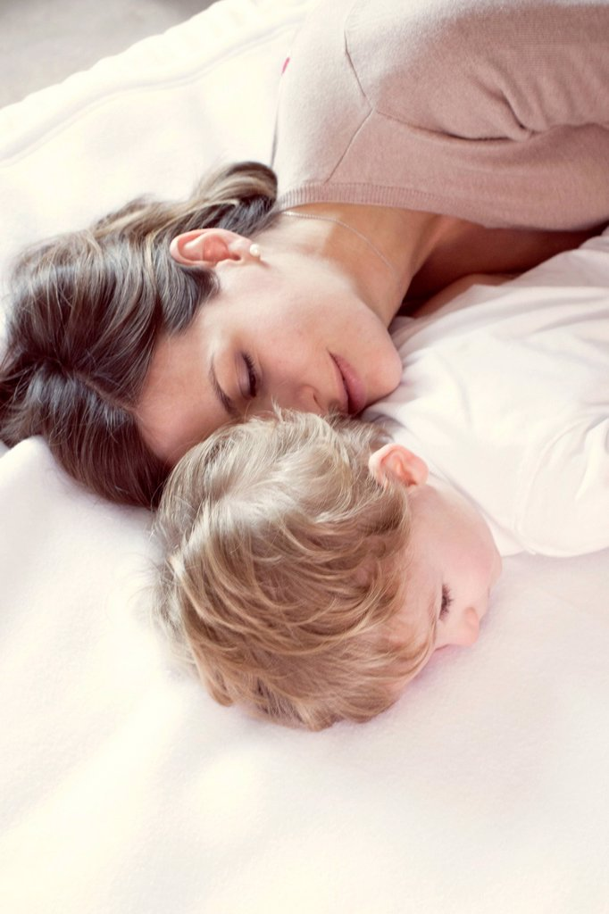 Mother napping with young son : Stock Photo