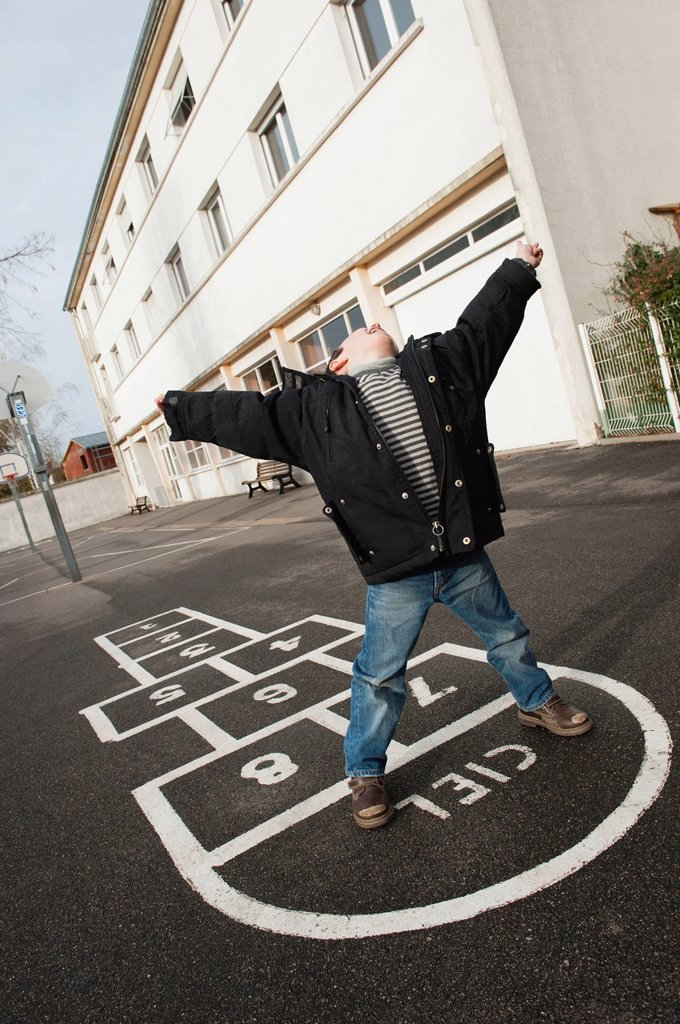 Stock Photo: 1569R-9073707 Boy playing hopscotch, tilt
