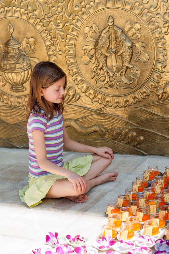 Girl sitting on floor in front of prayer candles : Stock Photo