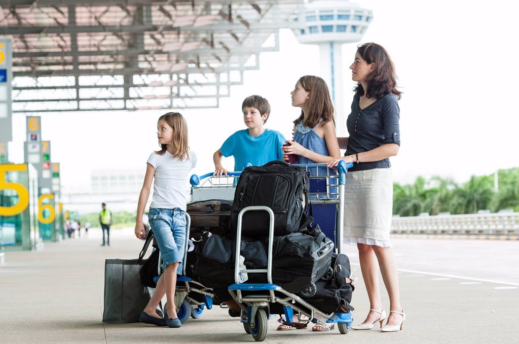 Stock Photo: 1569R-9074527 Family standing outside of airport with luggage
