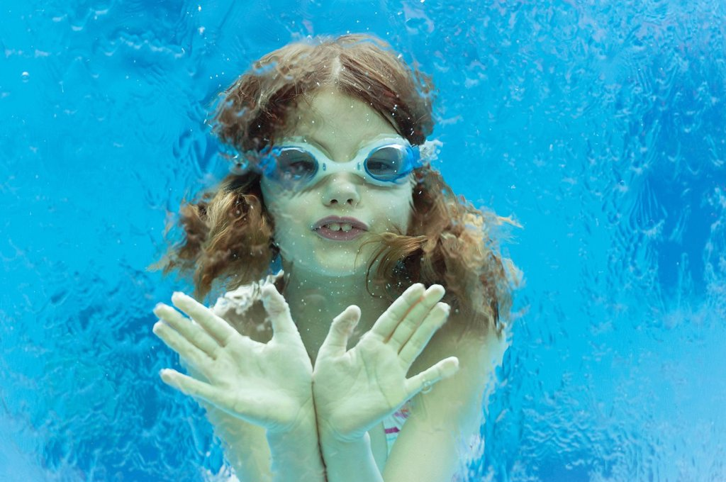 Stock Photo: 1569R-9074576 Girl wearing goggles swimming underwater in swimming pool