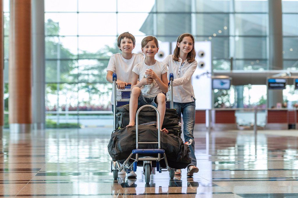 Stock Photo: 1569R-9074600 Brother and sister pushing younger sister on luggage cart in airport