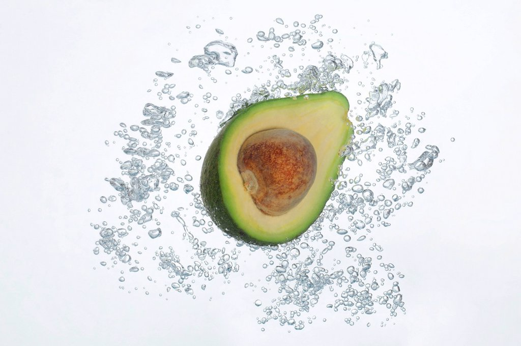 Avocado half submerged in sparkling water : Stock Photo