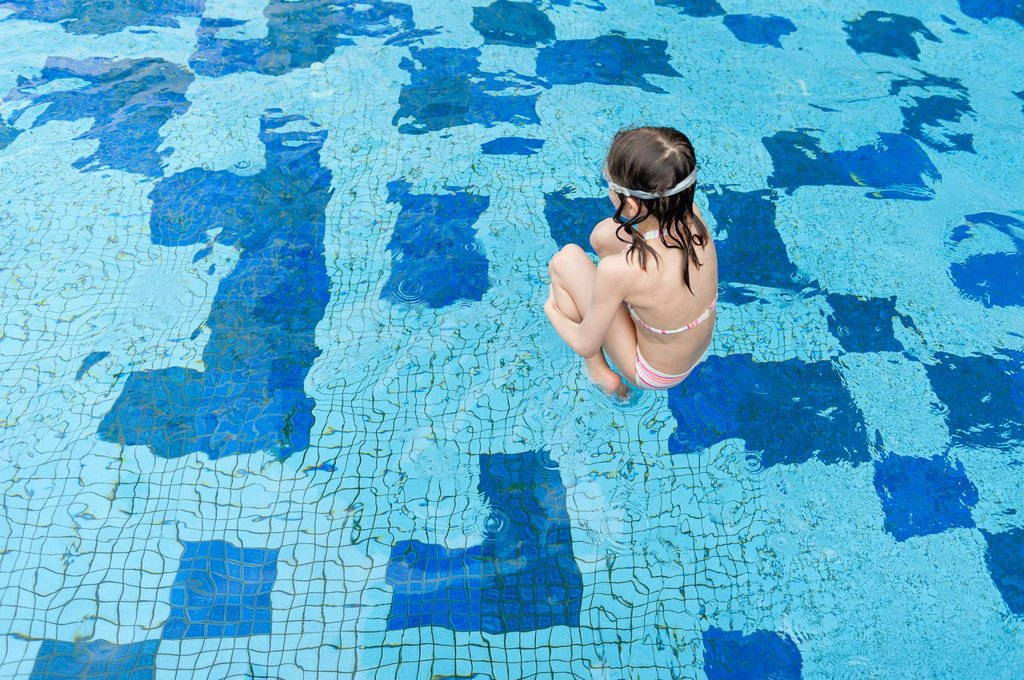 Stock Photo: 1569R-9074800 Girl jumping into swimming pool, rear view