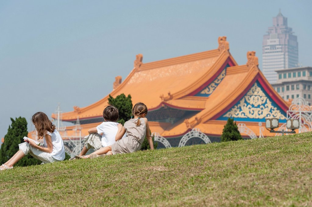 Children sitting on grass overlooking National Concert Hall, Chiang Kai_Shek Memorial Hall, Taipei, Taiwan : Stock Photo