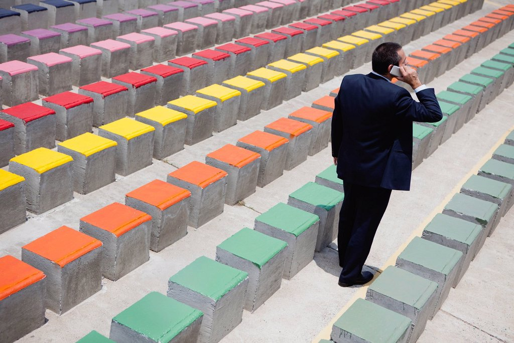 Stock Photo: 1569R-9074817 Business executive using cell phone by rows of bleachers, rear view