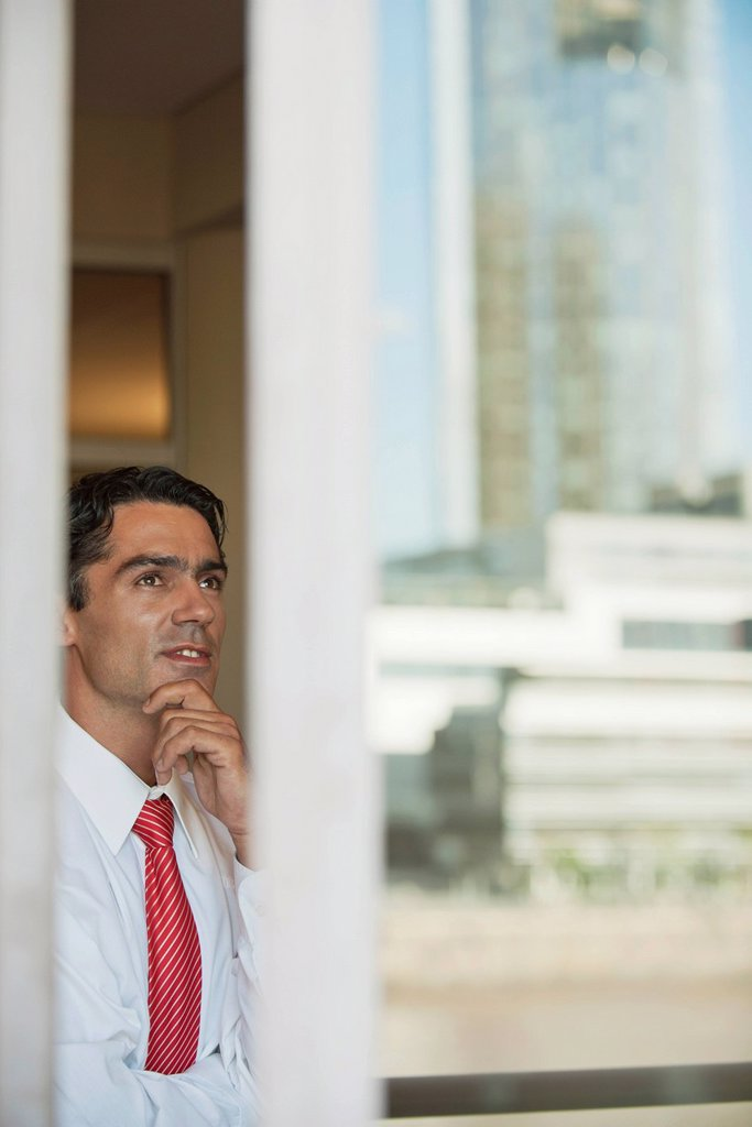 Stock Photo: 1569R-9074895 Businessman in office, seen from outside of window