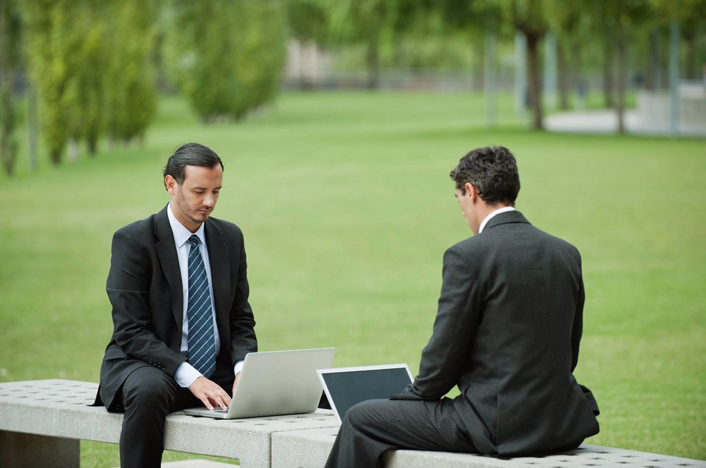 Stock Photo: 1569R-9074919 Businessmen using laptop computers outdoors