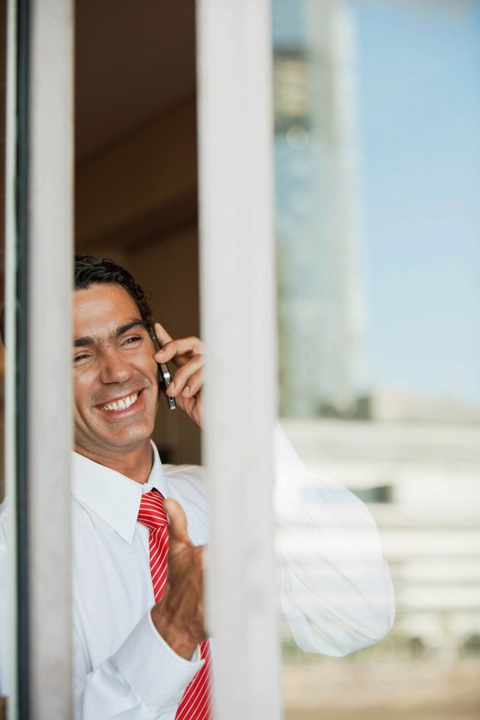 Businessman using cell phone in office, seen from outside of window : Stock Photo