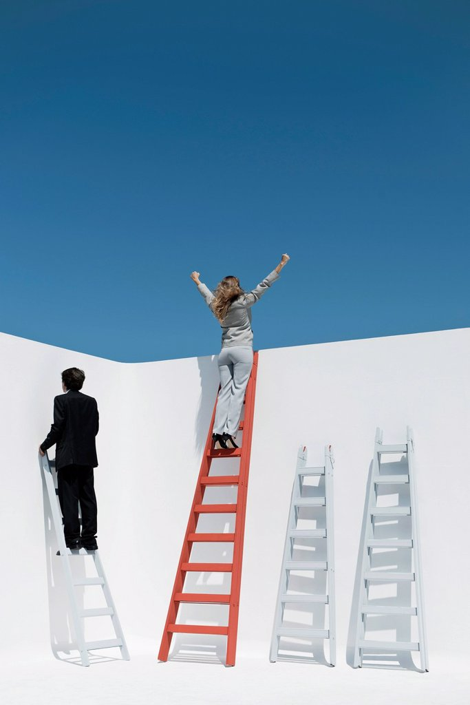 Businesswoman standing at top of ladder with arms raised in air : Stock Photo