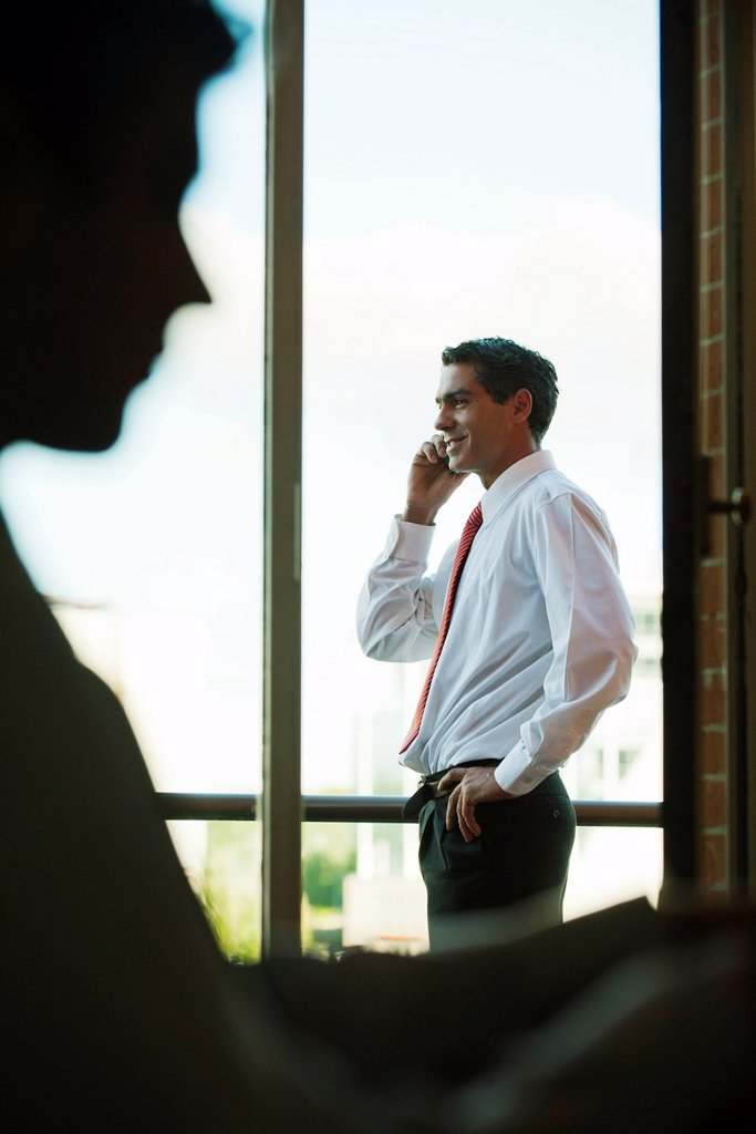 Stock Photo: 1569R-9075033 Silhouette of businessman using cell phone by window