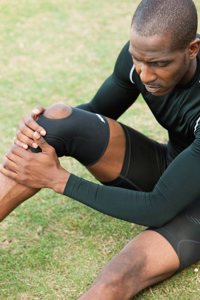 Male athlete wearing knee brace : Stock Photo
