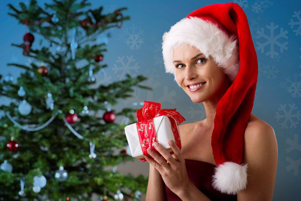 Woman wearing Santa hat and holding Christmas present, portrait : Stock Photo