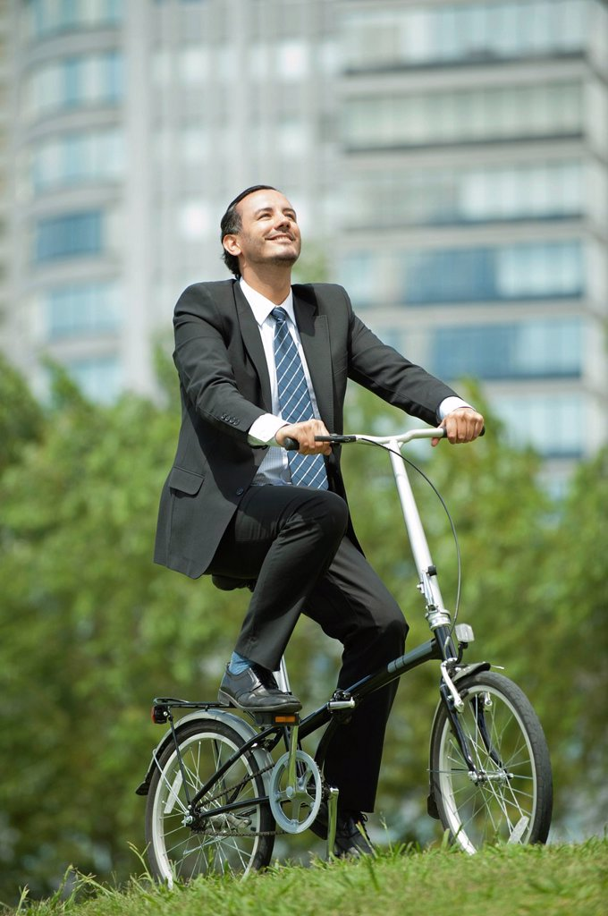Stock Photo: 1569R-9075264 Businessman riding bicycle