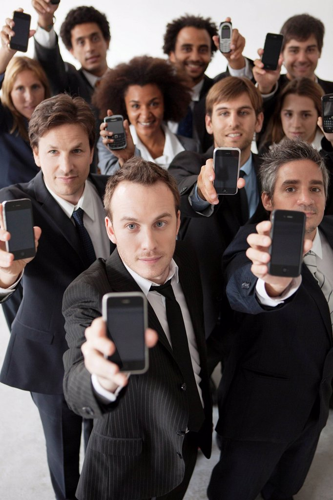 Business professionals holding aloft their cell phones : Stock Photo