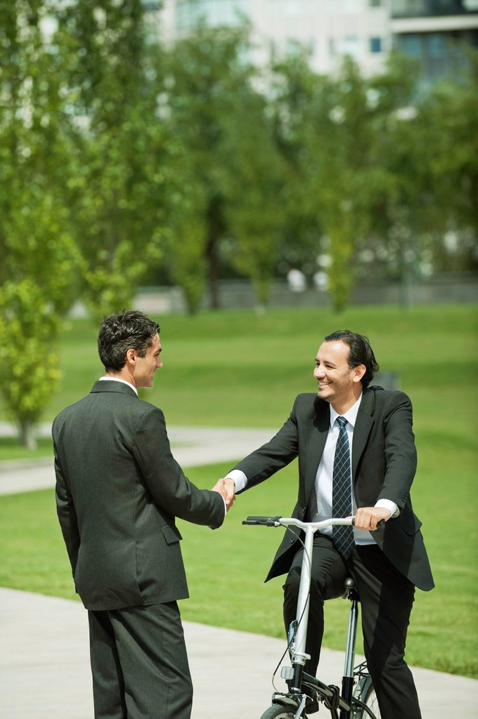 Stock Photo: 1569R-9075342 Businessmen greeting each other with handshake, one man on bicycle