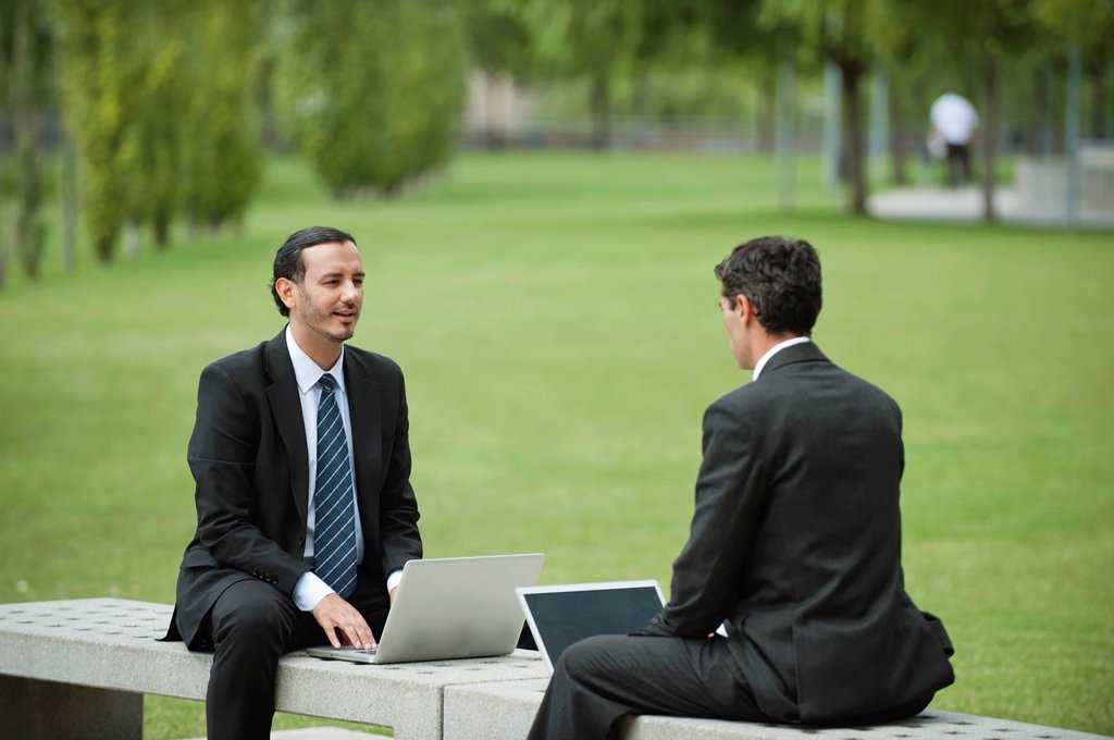 Stock Photo: 1569R-9075355 Business executives discussing work while using laptop computers outdoors