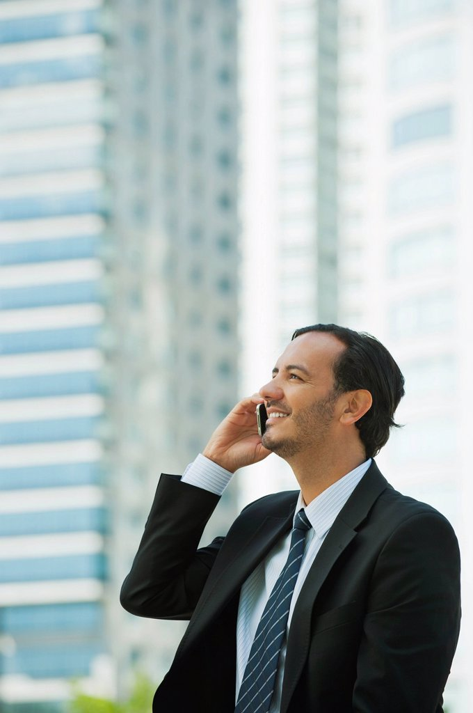 Stock Photo: 1569R-9075381 Business executive using cell phone outdoors