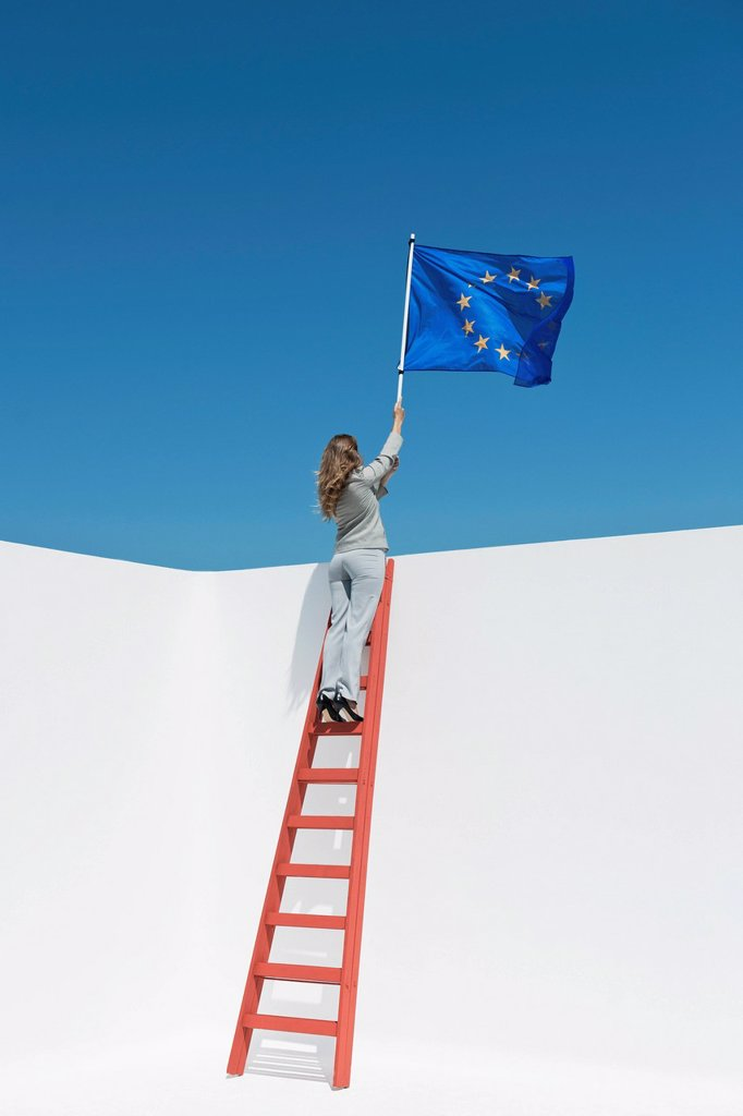 Stock Photo: 1569R-9075402 Businesswoman standing at top of ladder, holding European Union flag