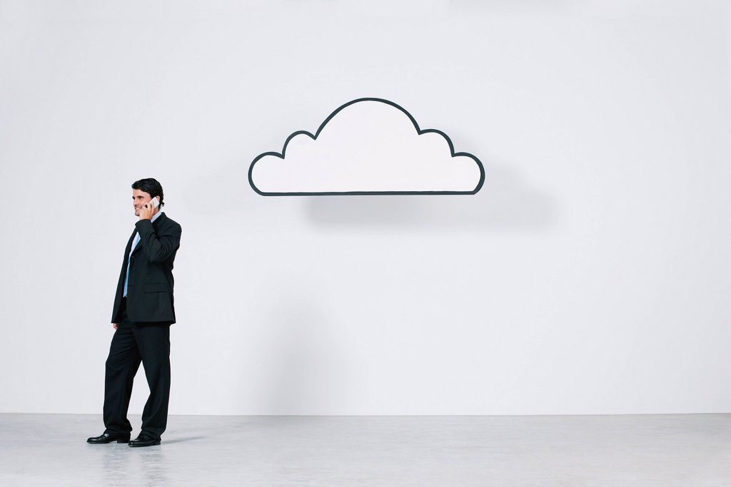 Businessman talking on cell phone near graphic cloud representing cloud computing : Stock Photo