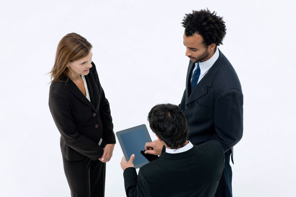 Stock Photo: 1569R-9075500 Business associates chatting while colleague uses digital tablet