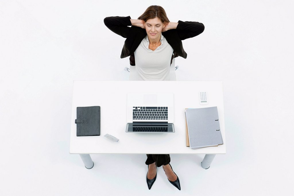 Businesswoman relaxing at desk with eyes closed : Stock Photo