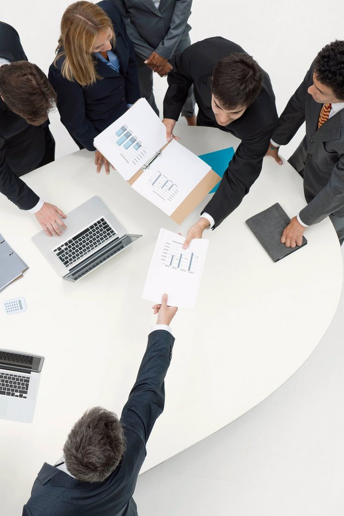 Business associates reviewing documents in meeting : Stock Photo