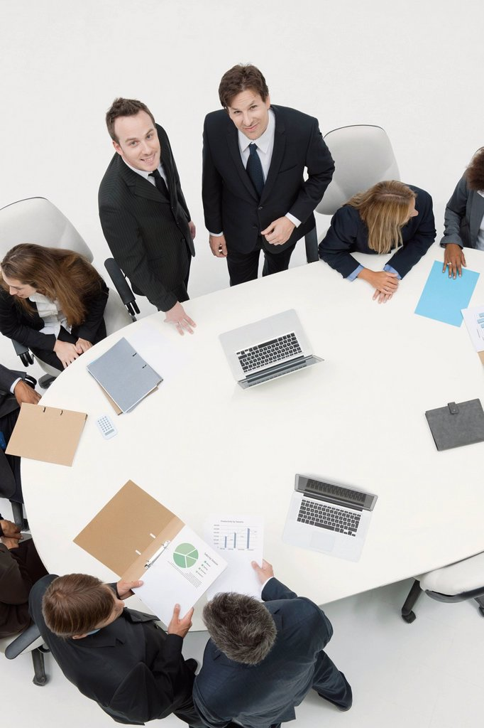 Businessmen working with associates at meeting : Stock Photo