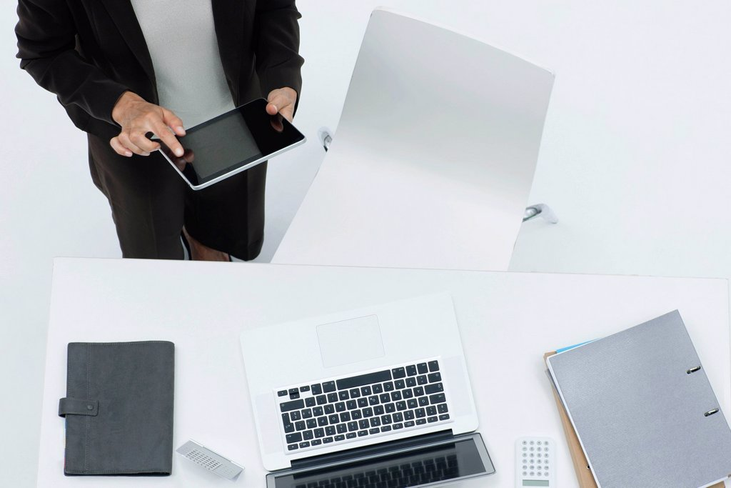 Businesswoman standing by desk using digital tablet, high angle view : Stock Photo