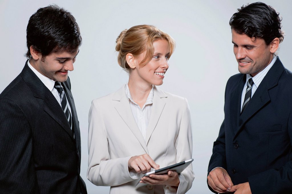 Stock Photo: 1569R-9075618 Executives looking at digital tablet together