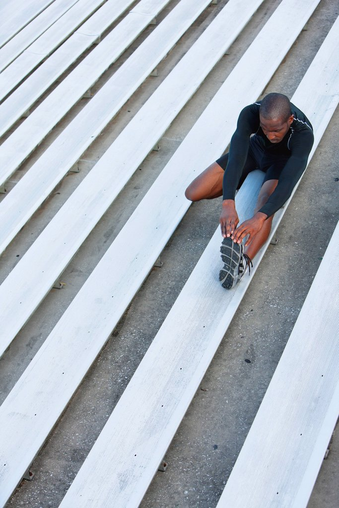Stock Photo: 1569R-9075664 Man stretching on bleacher, high angle view
