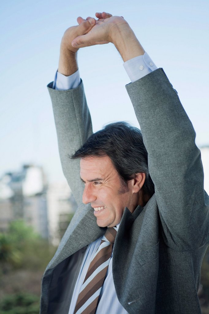 Stock Photo: 1569R-9075734 Mature businessman stretching arms outdoors