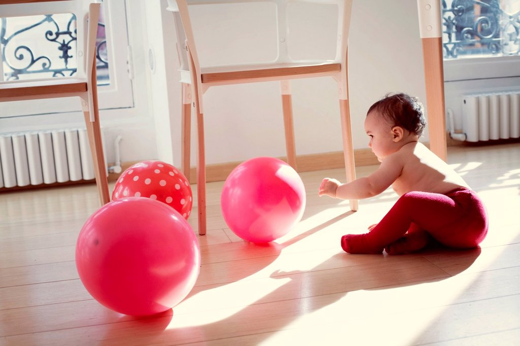 Stock Photo: 1569R-9075744 Infant playing with ballons